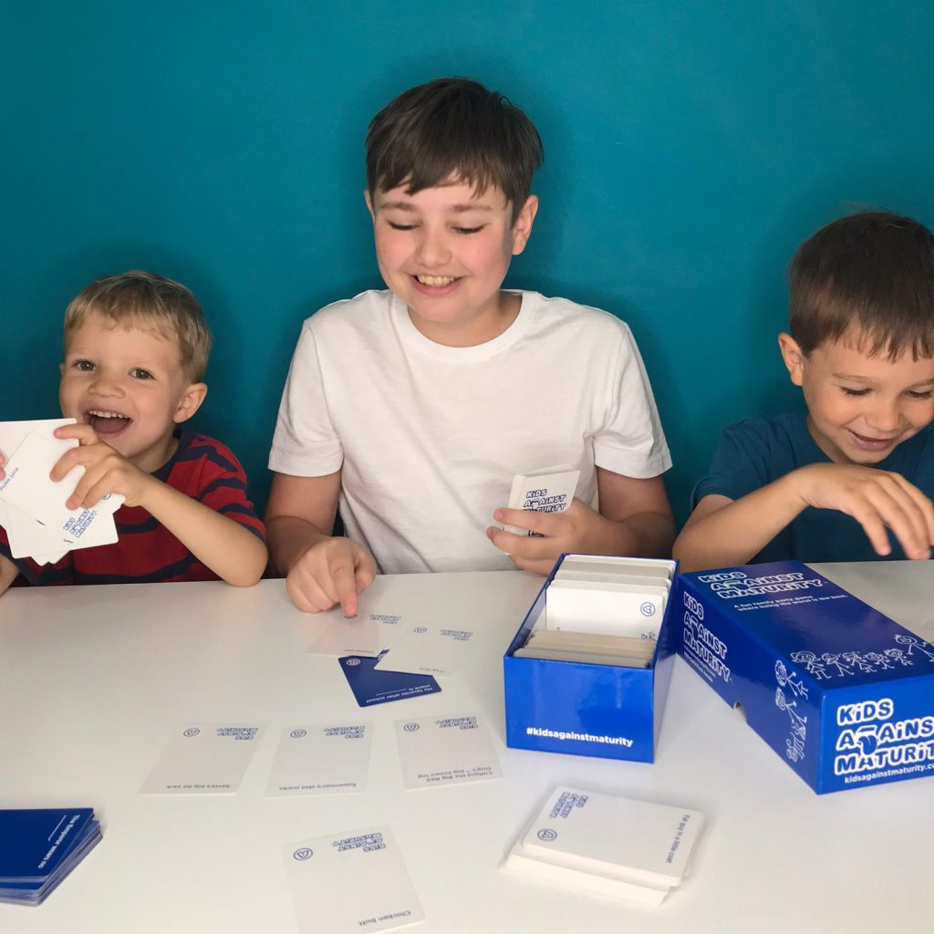 3 boys playing card game Kids Against Maturity